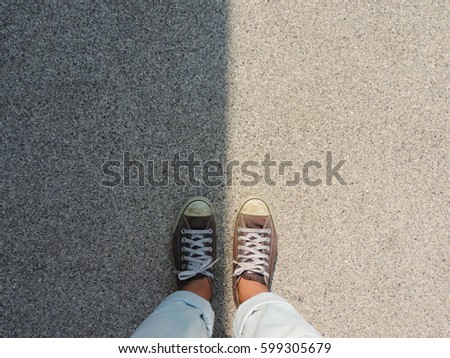 Top view of sneakers on the asphalt road,with dark side and bright side.