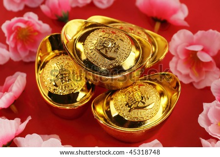 Top view of some chinese gold ingots surrounded by cherry blossoms on a red background