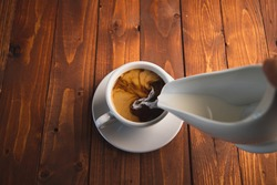 Top view of someone pouring cream in a black coffee in a white cup with copy space