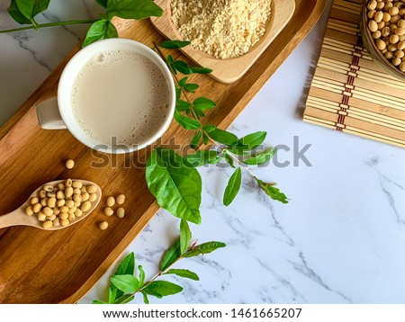 "Top view of soymilk cups,soybean seeds on wooden spoon and soy milk powder in a wooden plate background white marble table, is a healthy drink for women because of the ""isoflavones"" substance"