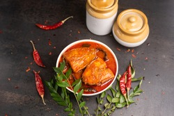 Top view of spicy and hot king fish curry with green curry leaf Kerala India. Barracuda Fish curry with red chili powder, coconut milk Asian cuisine.