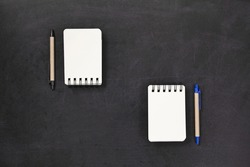 Top view of spiral blank craft paper cover notebook with pen on black
