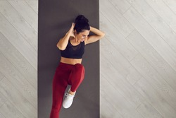 Top view of sporty active woman doing cross training bicycle crunches trains leg muscles and abs. Athlete conducts daily training on a mat in the room. Banner. Place for text. Article for website.