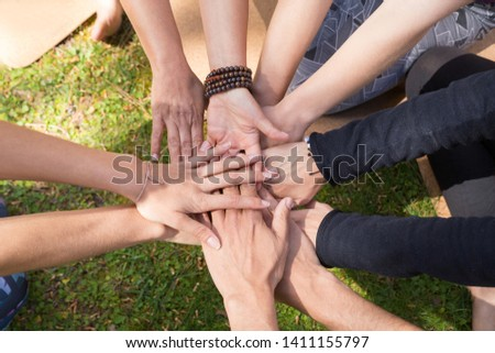 Top view of stack of hands against green grass. Friendship, teamwork or community gesture. Unity or team concept #1411155797
