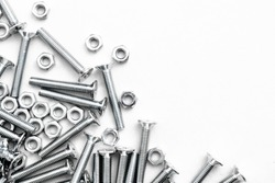 Top view of stainless steel bolts or iron nails on brigth white background with silver color.  Metal screws for use in sheet metal.