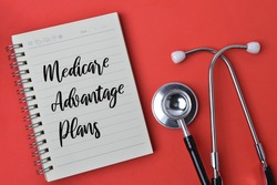 Top view of stethoscope and notebook written with text MEDICARE ADVANTAGE PLANS over red background.