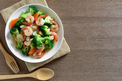 top view of stir fried broccoli with shrimps in a ceramic dish on wooden table. homemade style food concept.
