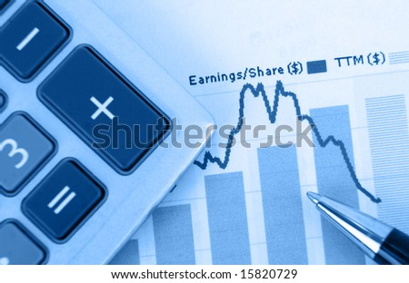 top-view of stock graph - focus is on graph with pen and calculator in foreground