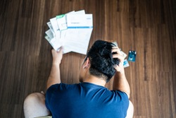 Top view of stressed young Asian man putting hands on head trying to find money to pay credit card debt and all loan bills. Financial problem from coronavirus or covid19 outbreak crisis concept.