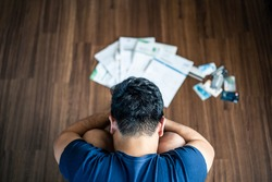 Top view of stressed young Asian man sitting and hugging knees, trying to find money to pay credit card debt and all loan bills. Financial problem from coronavirus or covid19 outbreak crisis concept.