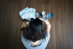 Top view of stressed young Asian woman hands holding the head trying to find money to pay credit card debt and all loan bills. Financial problem from coronavirus or covid-19 outbreak crisis concept.