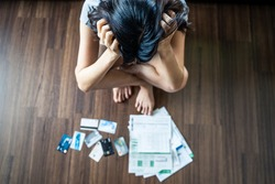 Top view of stressed young Asian woman putting hands on head, trying to find money to pay credit card debt and all loan bills. Financial problem from coronavirus or covid19 outbreak crisis concept.