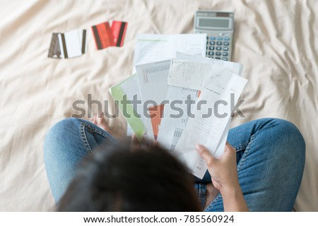 Top view of stressed young asian woman trying to find money to pay credit card debt.