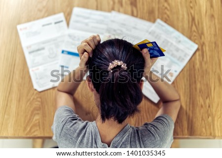Top view of stressed young sitting Asian woman hands holding the head worry about find money to pay credit card debt and all loan bills. Financial problem concept.