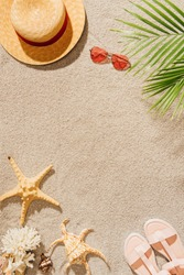 top view of stylish hat with sunglasses and sandals on sandy beach