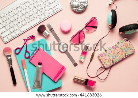 Top view of stylish  ladies lifestyle accessories. Pastel Colors Trend. Pink notebook, trendy  hearts sunglasses,turquoise headphones,brushes,lipstick,nail polish,keyboard on pink tender background.