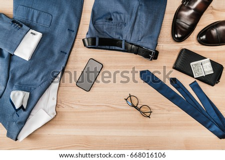 top view of suit and accessories with smartphone on wooden tabletop Foto stock ©