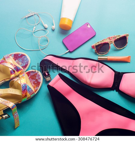 Top view of summer accessories for modern  stylish girl. Beach fashion set.Overhead of essentials for  young person. Neon shoes and bright colors.