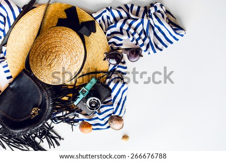 Top view of summer accessories for modern woman on her vacation. Straw hat,  camera, stylish sunglasses, black leather boho bag and striped beach dress on white floor.
