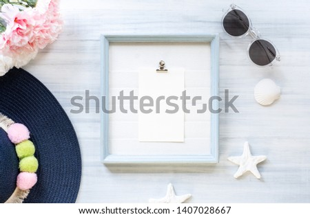 top view of summer blue female hat and picture frame with sunglasses and seashell and star fish decoration on white wood table.summer vacation