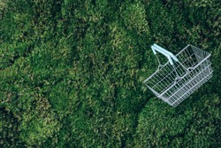 Top view of supermarket shopping basket on green grass, moss background. Minimalism style. Black friday sale, discount, shopaholism, ecology concept. Sustainable lifestyle, conscious consumption.