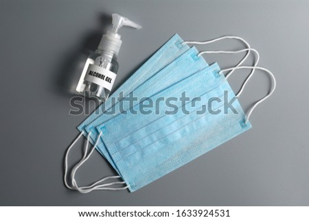 Top view of Surgical ear-loop masks and alcohol spray or anti bacteria spray on grey background. Personal hygiene concept.