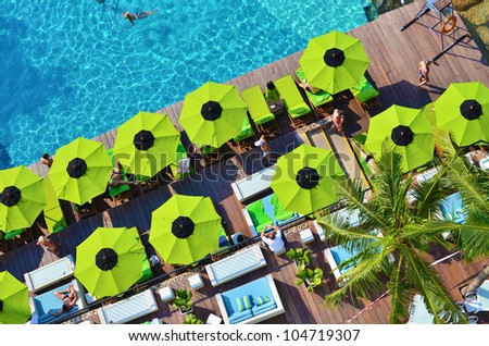Top view of swimming pool side with a seat and umbrella