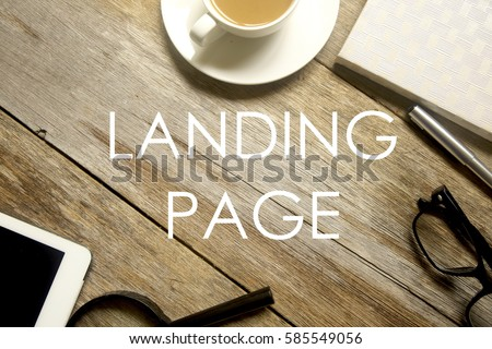 Top view of tablet pc,magnifying glass, notebook, pen, glasses and a cup of coffee with LANDING PAGE written on wooden table. #585549056