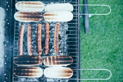 top view of tasty hot dogs grilling on bbq grill grade on green grass background
