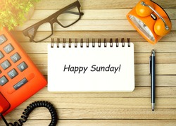 Top view of telephone, plant, eye glasses, alarm clock, pen and open notebook written with HAPPY SUNDAY! on wooden background. Business Concept.