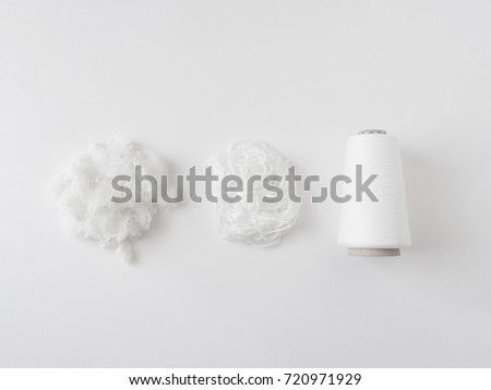 top view of Textile industry concept with yarn spools, fiber and Wool Roving on white background.
