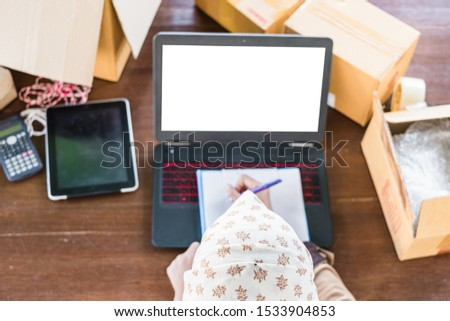 Top view of Thai young muslim startup online shop owner wearing hijab checking item orders using computer and  clipboard.