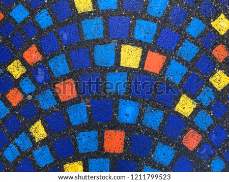 Top view of the asphalt pavement with painted multicolored rectangles. The rectangles are arranged in an arc in several rows. Background. Texture. #1211799523