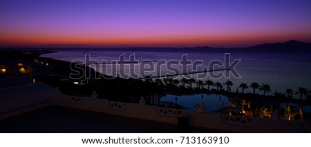 Top view of the coast of the tropical beach of Egypt in the popular tourist area of Sharm El Sheikh on background bay of the red sea and colorful sky on horizon. Africa, Egypt, sharm el sheikh #713163910