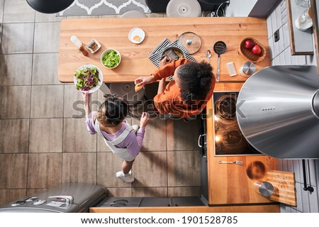 Top view of the happy curly multiracial woman giving a piece of cheese for her bestie while grated cheese at the pasta. Her bestie pouring salad at table. Friends cooking meal together at home. Stock Stock photo ©