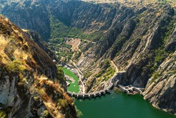Top view of the hydroelectric dam from the viewpoint of El Fraile, natural landscape with the valley and the Duero river. Flight of birds of prey, Salamanca, Spain