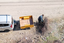 Top view of the man cutting the dried braches gathered in a pile with power saw near the car with yellow cargo trailer on cart road.