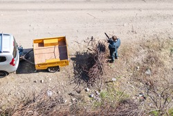 Top view of the man standing at the dried braches gathered in a pile and going to cut them. Car with yellow cargo trailer on cart road.