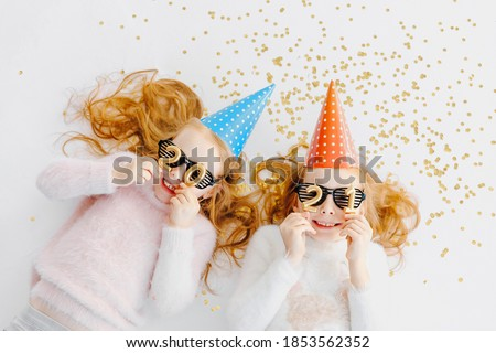 Top view of the new year two redheaded girls in red and blue caps and black glasses hold the numbers 2021
