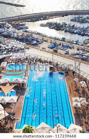 Top view of the out-door pool with swimming people in the blue water in autumn evening on the Mediterranean coast and marine background. Tel Aviv, Israel