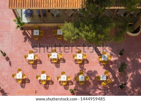 Top view of the outdoor restaurant summer terrace and yellow tables for visitors with nobody on them.