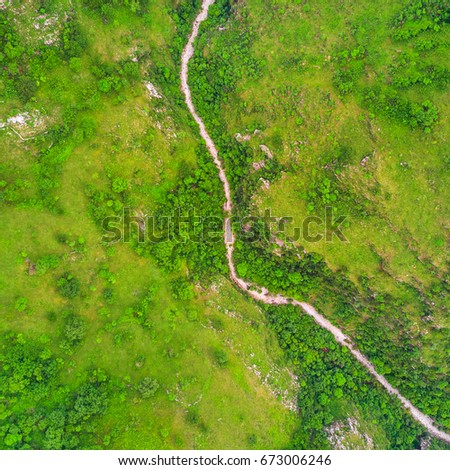 Top view of the river in the mountains surrounded by a green forest #673006246