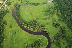 Top view of the river with turns of meanders and green forests in bright sunlight.