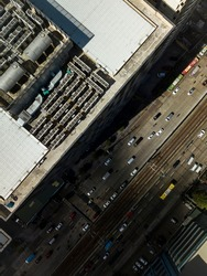 Top view of the roof deck of an office building, with installed VRF HVACs and water storage tanks. A large avenue with a rail system installed in the center lane.