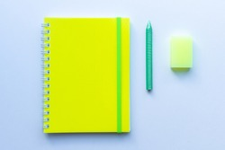 Top view of the set of stationery: yellow notepad with green stripe, green crayon pencil and yellow eraser on white background. Concept of education, business, minimalism.