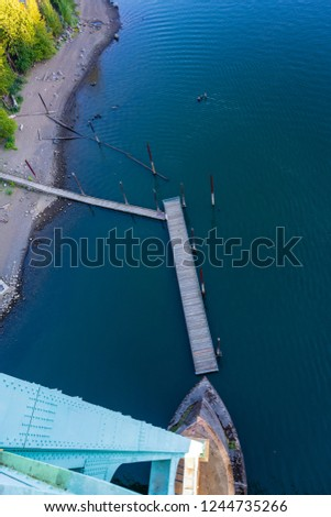 Top view of the support of the gothic St Johns bridge over the Willamette River in Portland with a small pier with pillars for mooring boats and yachts and part of the shore with autumn trees #1244735266