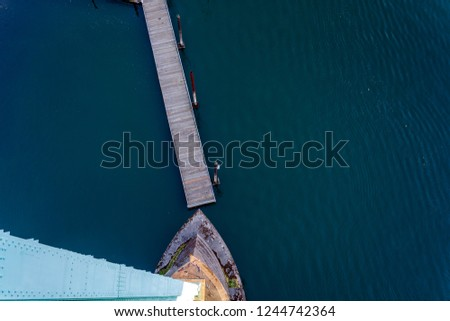 Top view of the support of the gothic St Johns bridge over the Willamette River in Portland with a small floating pier with pillars for mooring boats and yachts and dark water surface #1244742364