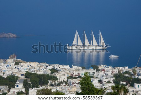 Top view of the town of Mykonos Island and a sailing ship in the blue sea ...