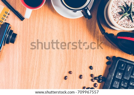 top view of  the wooden brown desk or brown table with many things ,a keyboard, a headphone, a cactus in the white flowerpot, a cup of coffee ,  many coffee beans ,a pen  and a camera for background #709967557