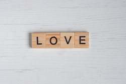 Top view of the word love laid out from square wooden tiles on old white wooden background. Concept of valentines day.